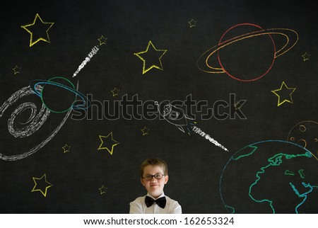 Thinking boy dressed up as business man with chalk universe planet solar system on blackboard imagining space travel - stock photo