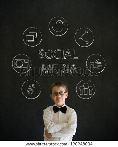 Thinking boy dressed up as business man with social media icons on blackboard background - stock photo