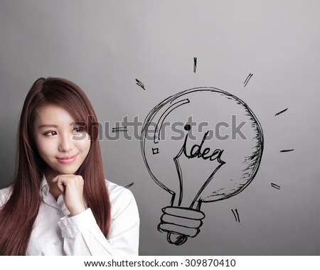 Thinking business woman and look idea lightbulb isolated on grey background, asian beauty - stock photo