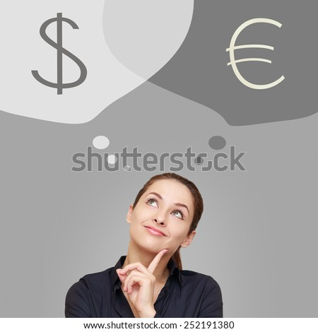 Thinking business woman looking up on dollar and euro currency on grey background - stock photo