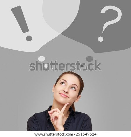 Thinking business woman looking up on question and exclamation signs in bubbles on grey background - stock photo