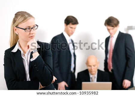 Thinking business woman standing in front of her colleagues; selective focus on woman - stock photo