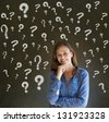 Thinking business woman with chalk questions marks on blackboard background - stock photo