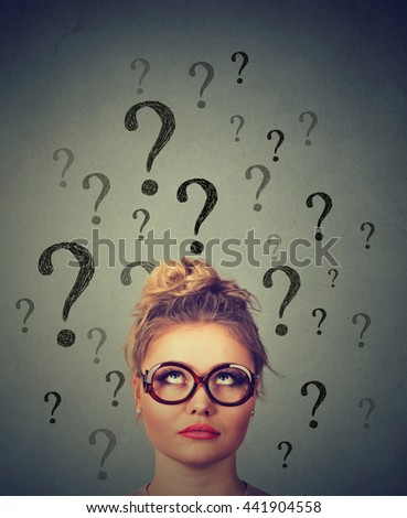 Thinking business woman with glasses looking up at many questions marks above head isolated on gray wall background - stock photo