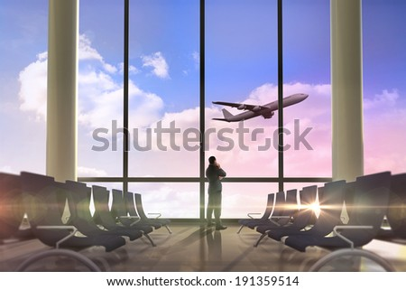 Thinking businessman against airplane flying past departures lounge