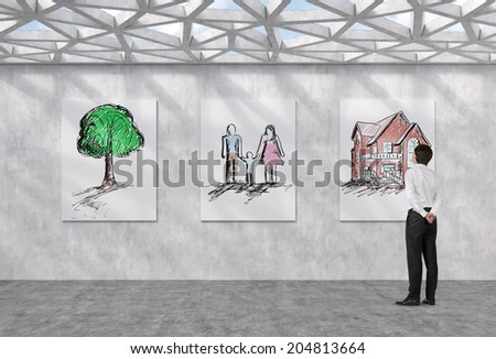 Thinking businessman and a concept of a dream life: three pictures on the wall - a family, a tree and a house.  - stock photo