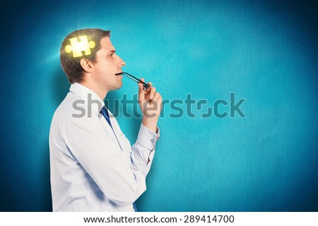 Thinking businessman biting glasses against blue background