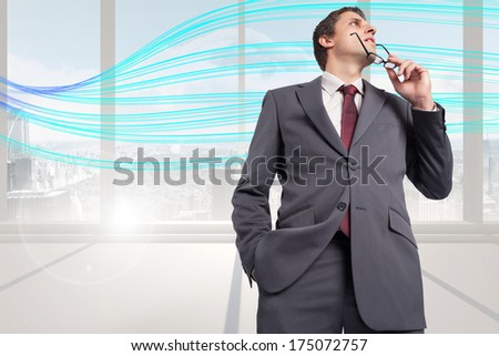 Thinking businessman holding his glasses against abstract blue line design in room