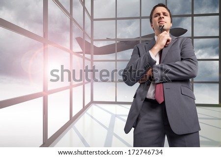 Thinking businessman holding his glasses against airplane flying past window
