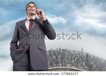 Thinking businessman holding his glasses against curved cityscape