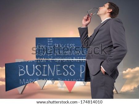 Thinking businessman holding his glasses against red and grey arrows pointing against sky - stock photo