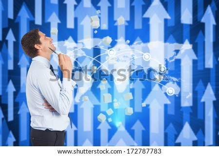 Thinking businessman holding pen against futuristic arrow pointing upwards