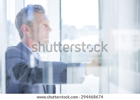 Thinking businessman in the office looking through the window - stock photo