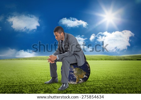 Thinking businessman sitting against sunny green landscape