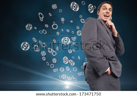 Thinking businessman touching his chin against cogs and wheels - stock photo