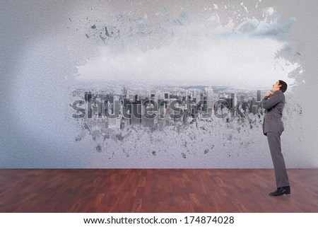 Thinking businessman with hand on chin against splash on wall revealing cityscape