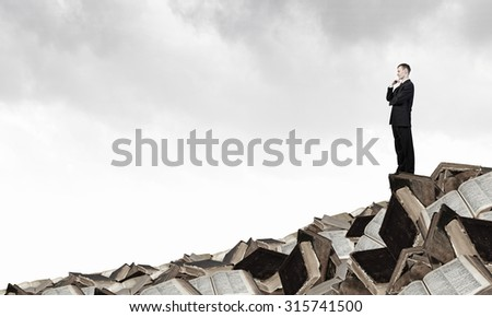 Thinking businessman with hand on chin on pile of old books - stock photo