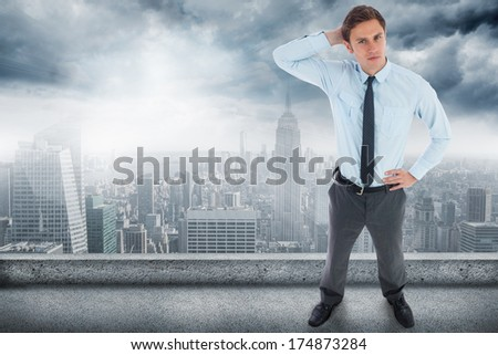 Thinking businessman with hand on head against balcony overlooking city