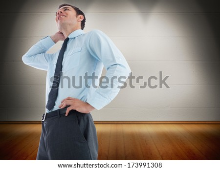 Thinking businessman with hand on head against room with wooden floor