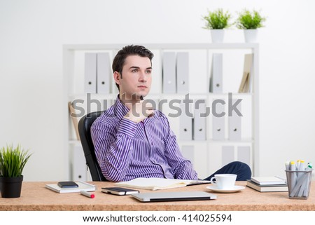 Thinking caucasian businessman sitting at desk with various items in office - stock photo