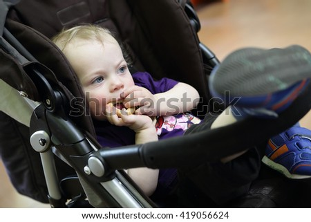 Thinking child eating bagel in a stroller - stock photo