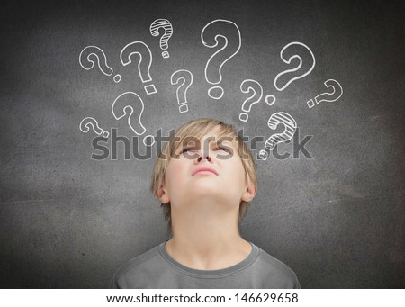 Thinking child looking at question marks above his head - stock photo