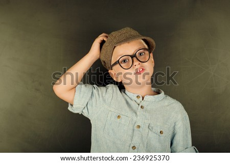 Thinking child with thick eyeglasses at a blackboard in the background  - stock photo