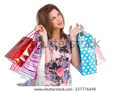 Thinking cute brunette holding shopping bags on white background