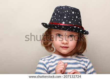Thinking cute kid in fashion hat with surprising look on empty copy space - stock photo