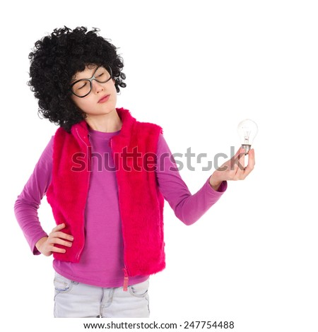 Thinking girl in curly wig and black glasses holding and looking at a light bulb. Waist up length studio shot isolated on white.