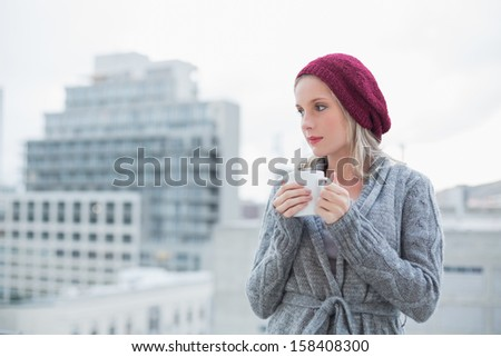 Thinking gorgeous blonde drinking coffee outdoors on urban background - stock photo
