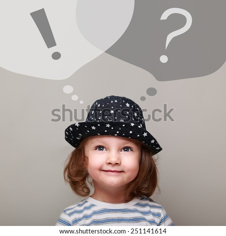 Thinking happy kid girl looking up on question and exclamation signs on grey background. Creativity business concept  - stock photo