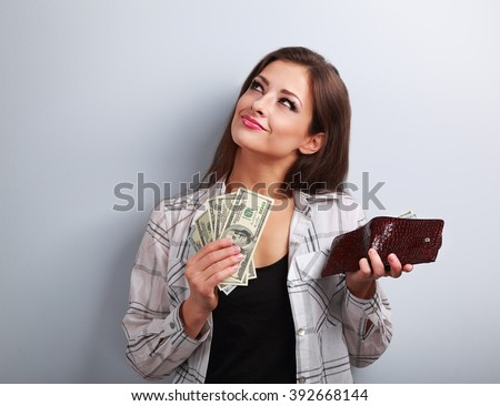 Thinking happy woman holding dollars and wallet in hands and want to spend money on blue background - stock photo