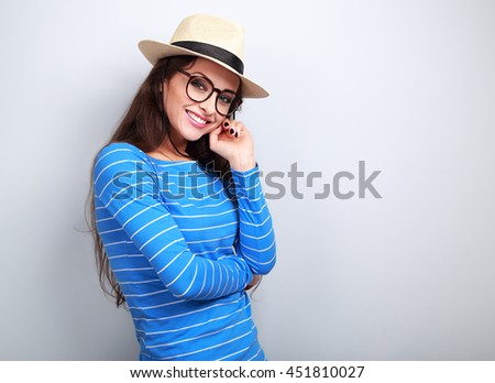 Thinking happy young woman in hat and glasses looking with smiling on blue background