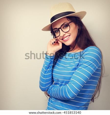 Thinking happy young woman in hat and glasses looking with smiling. Toned closeup portrait