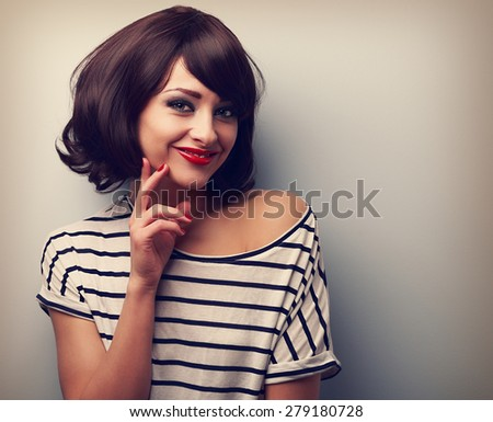 Thinking happy young woman with short hair looking on blue background with empty copy space. Vintage closeup color portrait - stock photo