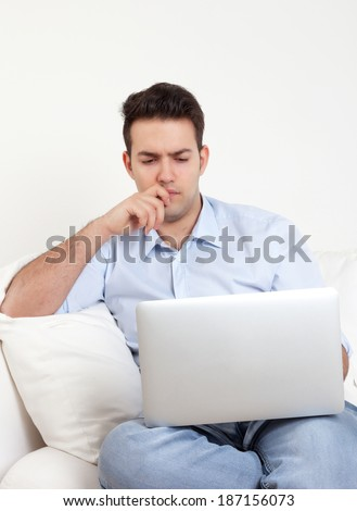 Thinking hispanic guy with notebook on a sofa