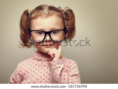 Thinking little kid girl looking happy wearing glasses. Vintage portrait - stock photo