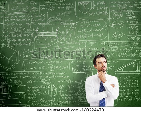 thinking man against desk with formulas - stock photo