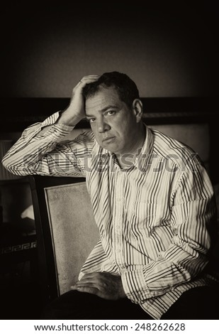 Thinking man sitting on a chair. Black and white portrait  - stock photo