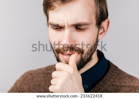 thinking man with beard in brown sweater finger in mouth - stock photo