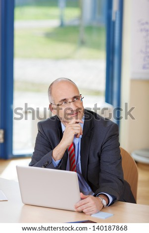Thinking mature businessman looking up, with laptop at office desk - stock photo