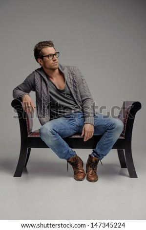 Thinking of the future. Handsome young men in glasses sitting on the chair and looking away while isolated on grey - stock photo