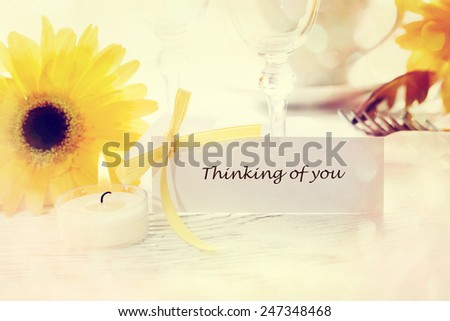 Thinking of you message card with table setting and yellow gerberas - stock photo