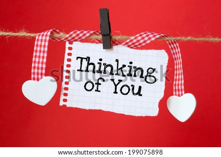 Thinking of You message written on a paper hanging on the clothesline on red background with two paper hearts - stock photo