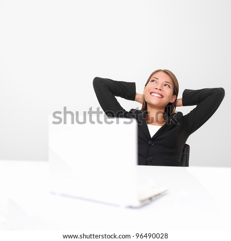 Thinking office worker day dreaming looking up smiling happy. Young business woman in suit sitting at office desk with laptop. Young mixed race Asian / Caucasian businesswoman. - stock photo