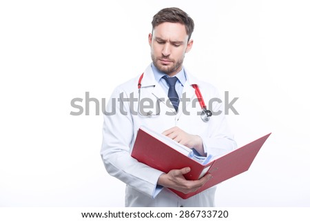 Thinking out loud. Thoughtful doctor holding folder and searching for information and keeping his eyes down. - stock photo
