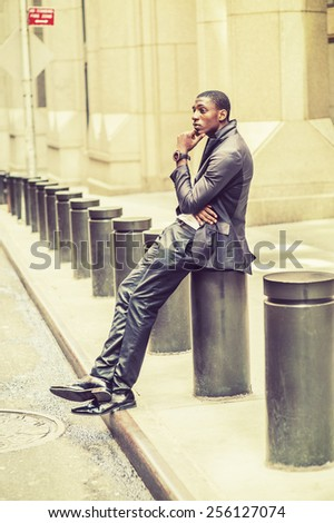 Thinking Outside. Young black college student sitting on street, hunchbacked, hand touching his chin, crossing legs. Concept of teenagers questioning life, career, self esteem. Retro filtered look. - stock photo
