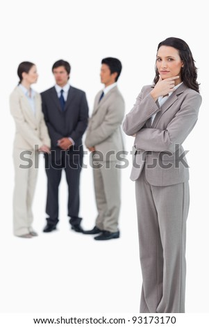 Thinking saleswoman with team behind her against a white background