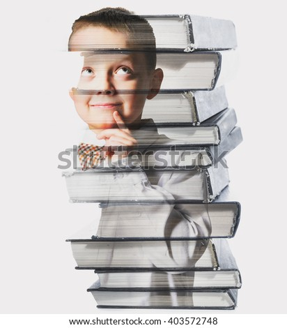 thinking school boy mixed with pile of books, against gray background - stock photo